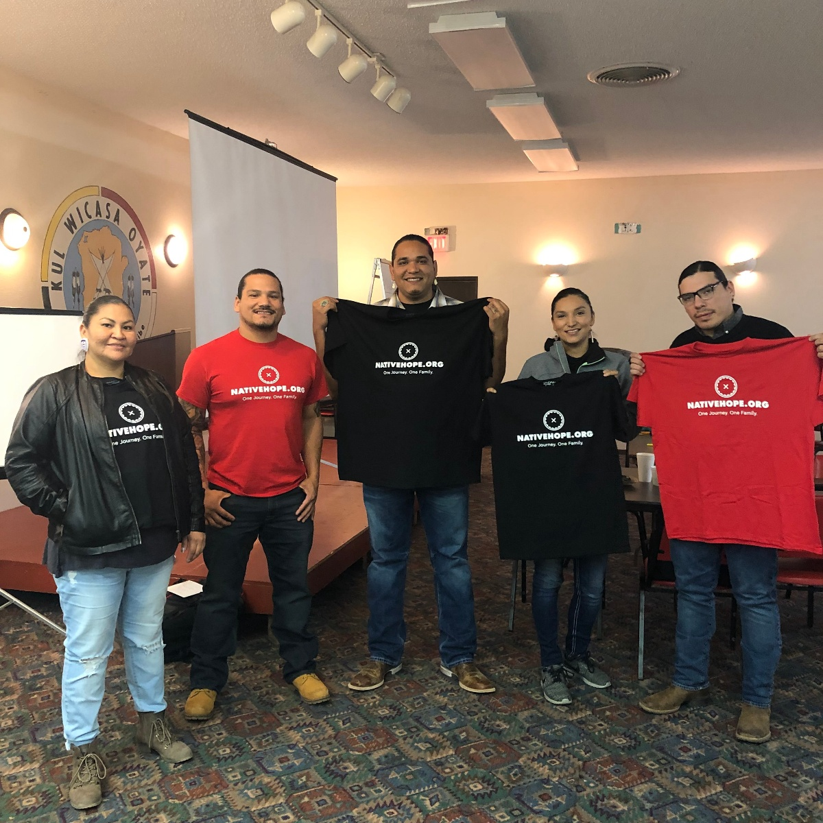 smiling group of people holding native hope shirts